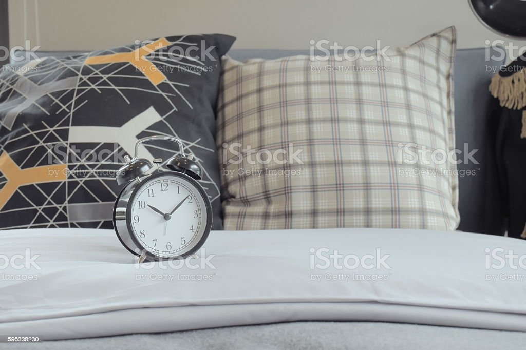 Classic style clock and grapic pattern pillows on white bed Lizenzfreies stock-foto