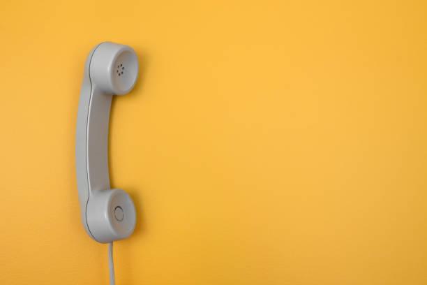 klassische telefonhörer auf leuchtend gelbem hintergrund - typisch 90er stock-fotos und bilder