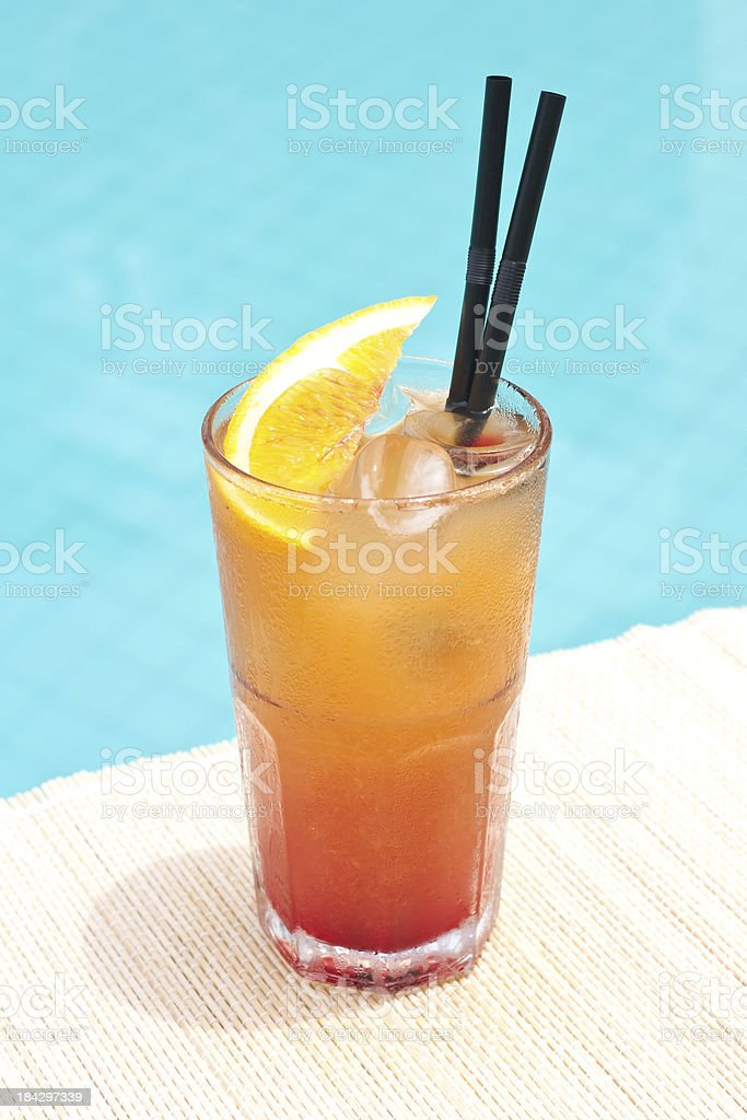 Classic Tequila Sunrise cocktail near waterpool on the mat stock photo