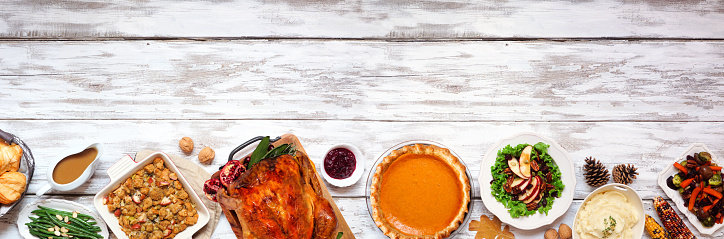 Classic Thanksgiving turkey dinner. Above view bottom border on a rustic white wood banner background with copy space. Turkey, mashed potatoes, stuffing, pumpkin pie and sides.