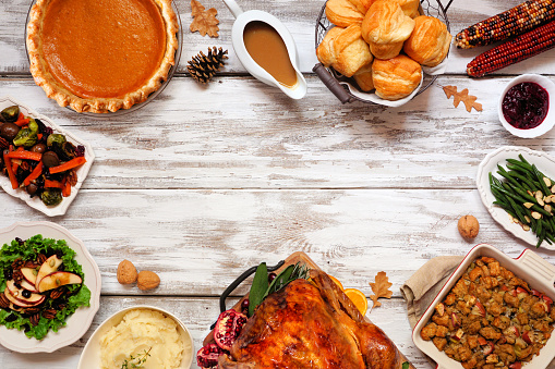 Classic Thanksgiving turkey dinner. Top down view frame on a rustic white wood background with copy space. Turkey, mashed potatoes, dressing, pumpkin pie and sides.