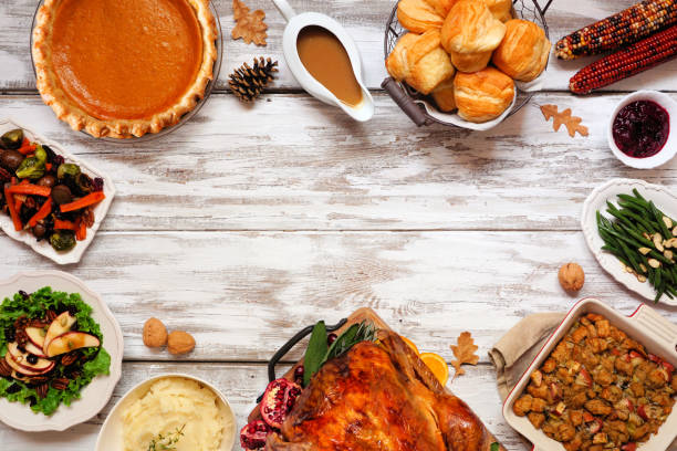 Classic Thanksgiving turkey dinner. Top down view frame on a rustic white wood background. stock photo