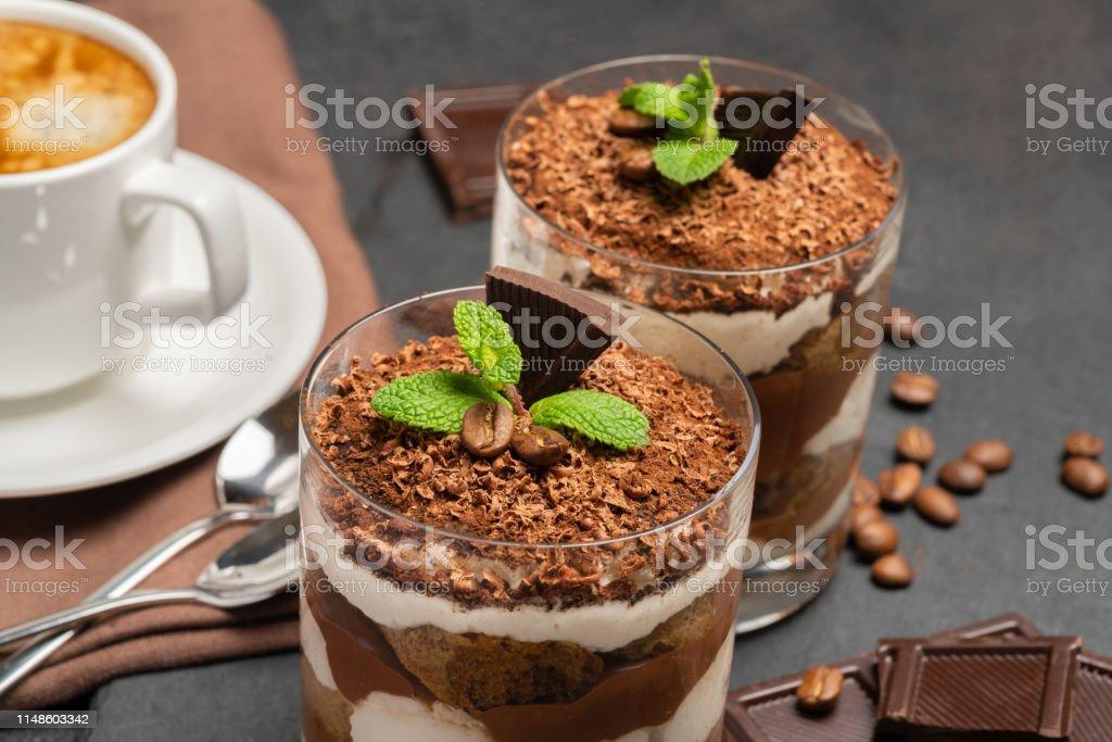 Classic tiramisu dessert in a glass and cup of coffee on dark...