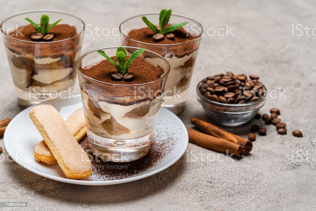 Classic tiramisu dessert in a glass cup and savoiardi cookies on...