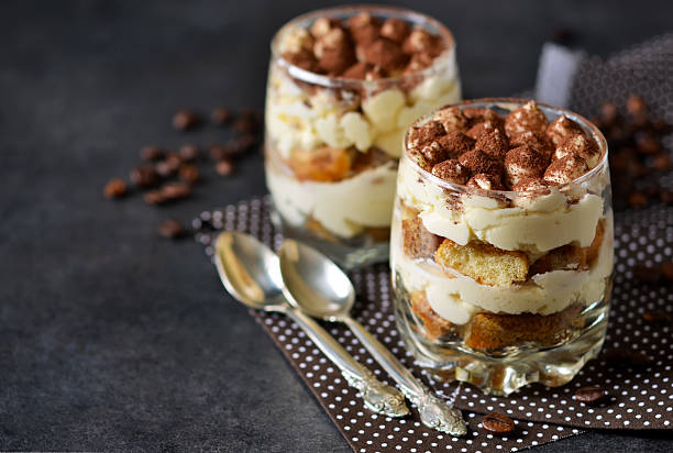 Classic tiramisu in a glass jar on the background chermon Classic tiramisu in a glass jar on the background chermon tiramisu stock pictures, royalty-free photos & images
