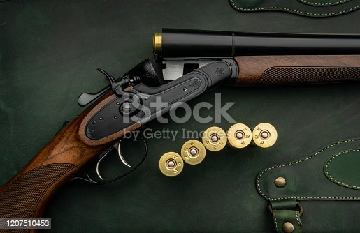 Classic trigger double-barreled hunting rifle on a green background. Smooth-bore hunting rifle open for reloading. Concept postcards for hunters.