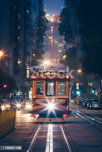 Classic view of historic traditional Cable Cars riding on famous California Street at night with city lights, San Francisco, California, USA