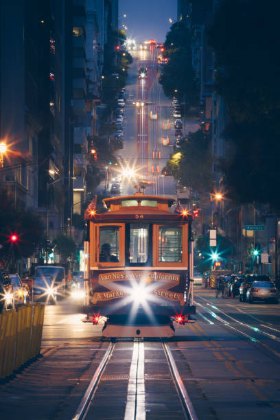 classic view of historic traditional cable cars riding on famous california street at night with city lights, san francisco, california, usa - são francisco califórnia imagens e fotografias de stock