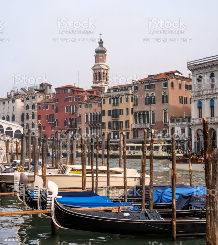 Classic view of the Venetian canal. Nm the foreground of the gondola and the high mooring pillars. stock photo