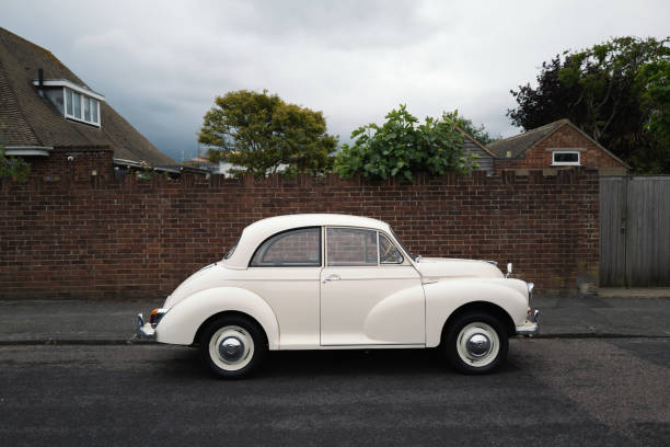 A classic vintage car, A white Morris Minor 1000 parked in front of a red brick road on a residential  street stock photo