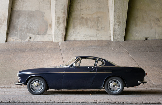 Stoke Poges, Buckinghamshire - May 7, 2021: A dark blue Volvo 1800S from 1967 sitting at the side of the road in a motorway underpass. The car was made famous in the sixties when Roger Moore drove a white example in the tv show