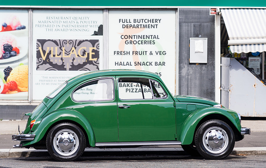 Glasgow, Scotland - Side view of a vintage Volkswagen Beetle, parked on a street in Glasgow's Southside.