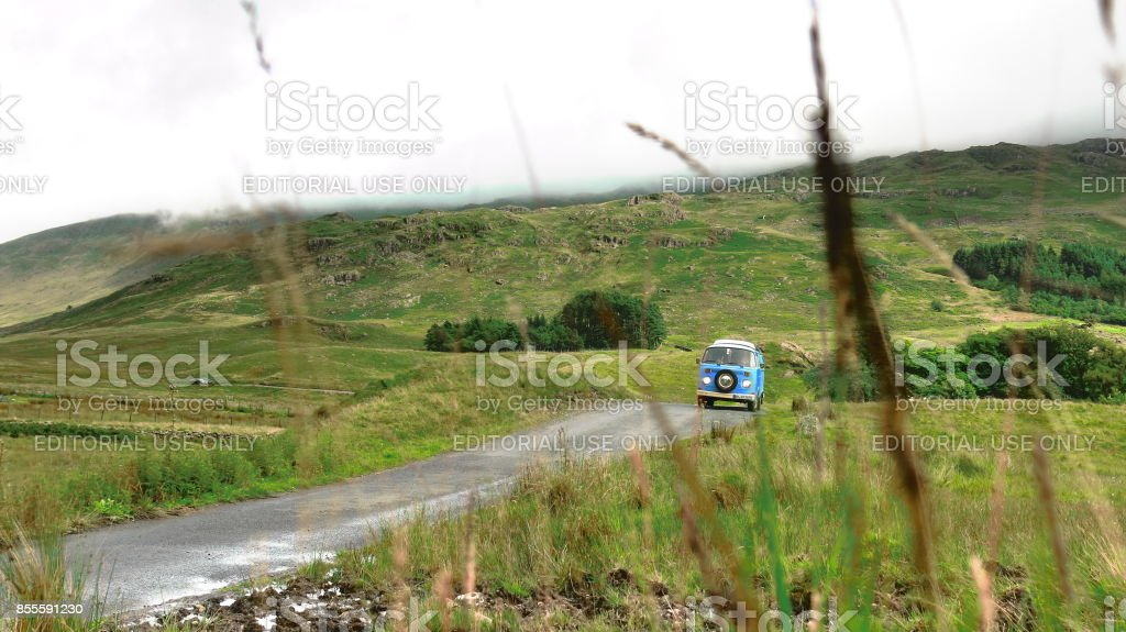 Classic VW Bus driving in the mountains of Lake District National Park, England stock photo
