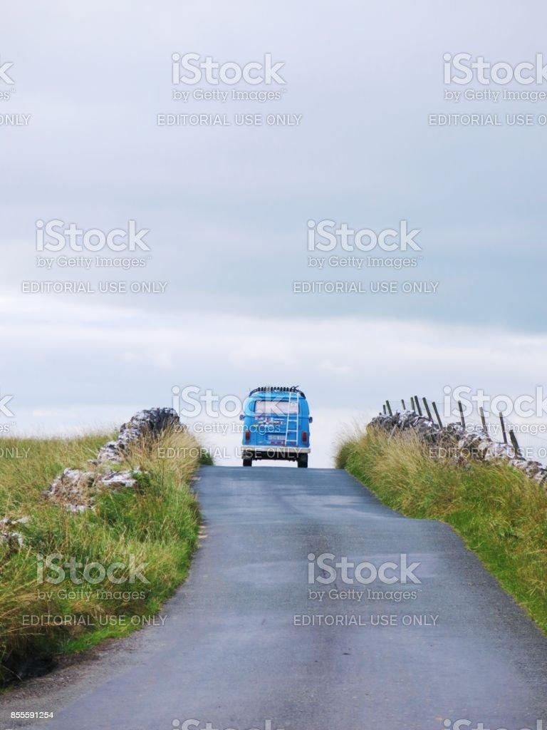 Classic VW Bus driving towards horizon on small english road stock photo