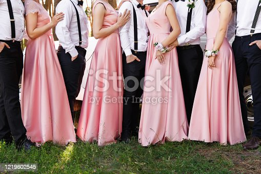 Classic wedding. Bridesmaids in pink dresses and groomsmen in black trousers and white shirts with suspender at wedding day