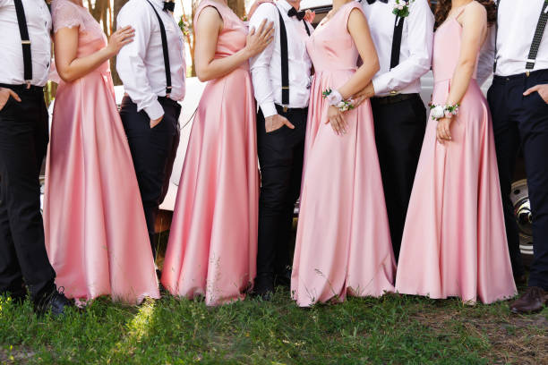 Classic wedding. Bridesmaids in pink dresses and groomsmen in black trousers and white shirts with suspender at wedding day stock photo