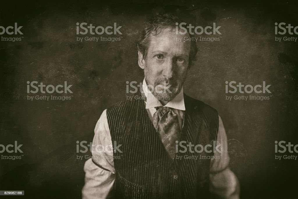 Classic wet plate photo of man with beard in vintage 1900 western clothing. stock photo