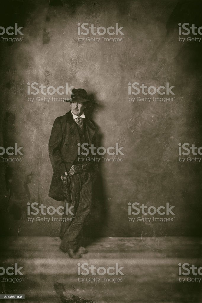 Classic wet plate photo of mysterious 1900 western man standing against wall. stock photo