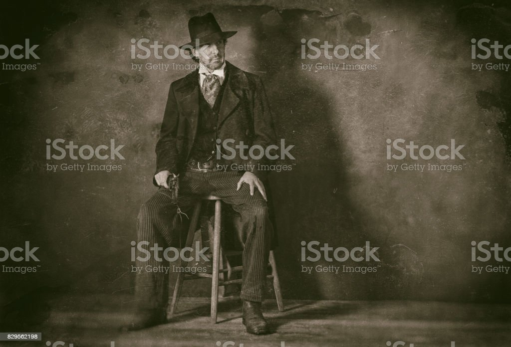 Classic wet plate photo of vintage 1900 western mature man with revolver sitting on wooden stool. stock photo