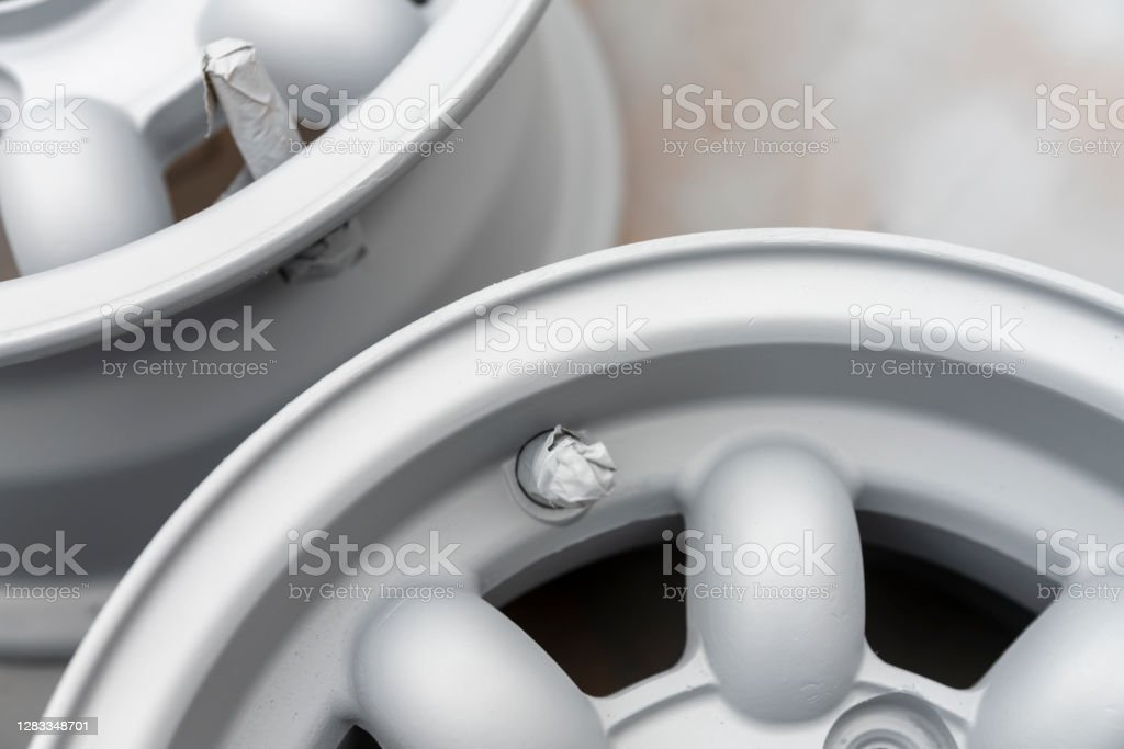 Classic wheel rim refurbishment These are the wheel.  This is a close-up of the rims after an initial clean and sand and with the first coat of primer applied. 2020 Stock Photo