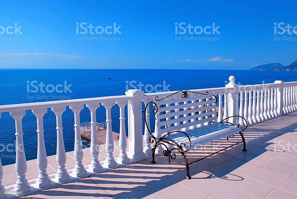 classic white balustrade, bench and empty terrace overlooking sea stock photo