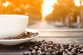 classic white coffee cup with hot coffee steam on a vintage dark black wooden table decoration with brown roasted coffee beans on natural green leaf background and sunlight bokeh in morning relax time