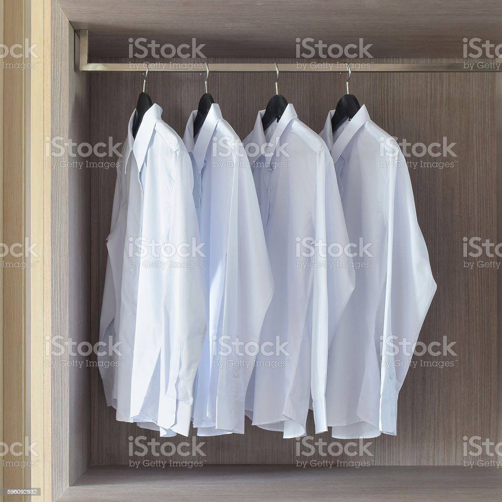 Classic white shirts in warm wooden wardrobe royalty-free stock photo
