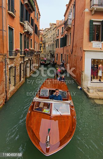 Venice, Italy-September 28, 2019: Classic wide-angle view of wooden Taxi boat in narrow city canal. The fastest and most convenient transport in Venice. Several gondolas in the background.