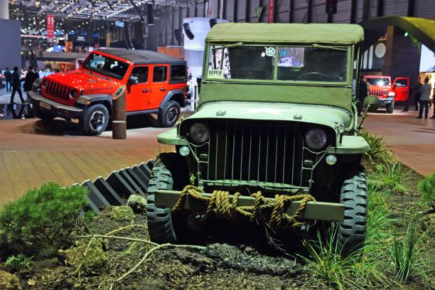 Classic Willys MB on the exposition Geneva, Switzerland, March 6th, 2018: The presentation of classic Willys MB Jeep on the motor show. This model was debut in 1941. On the back of the car we see the newest Jeep Wrangler generation. willys stock pictures, royalty-free photos & images
