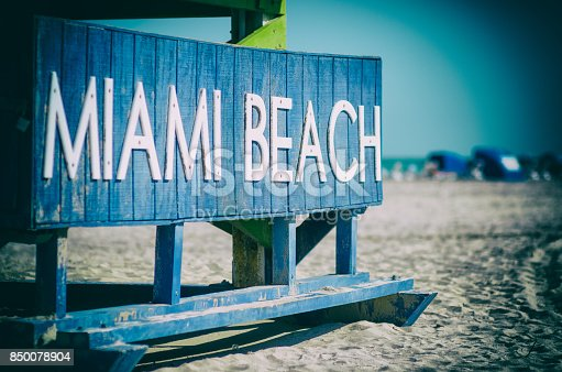 Classic wooden lifeguard hut standing under bright tropical sunlight on South Beach in Miami, Florida