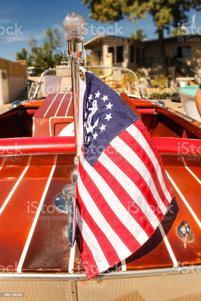 Classic wooden speed boat with nautical flag docked in front of a house on the lake - view from back with flag in focus zbiór zdjęć royalty-free