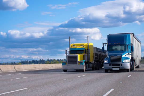 klassische gelbe und blaue moderne halb lkwas nebeneinander auf der straße - aufgemotzte trucks stock-fotos und bilder