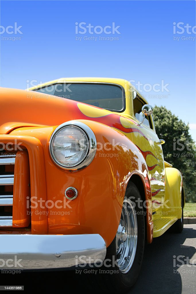Classic yellow truck painted in orange flames stock photo