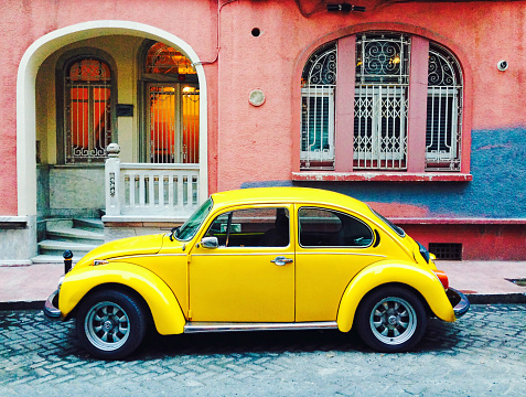 Istanbul, Turkey - January 13, 2015: Old yellow Volkswagen Beetle car parked on in the street. The Volkswagen Beetle was an economy car produced by the German auto maker Volkswagen from 1938 until 2003.