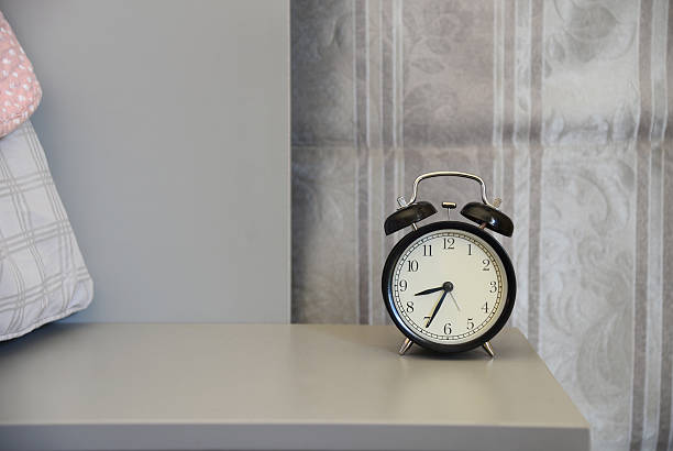 classical alarm clock on bedside table stock photo