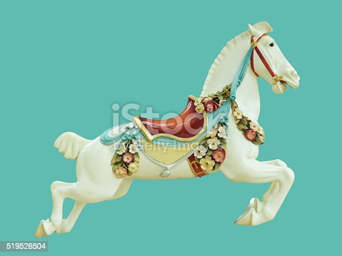 A classical antique styled white carousel horse for children and baby, decorated with saddle, flowers, and ribbon, isolated on a turquoise blue background.