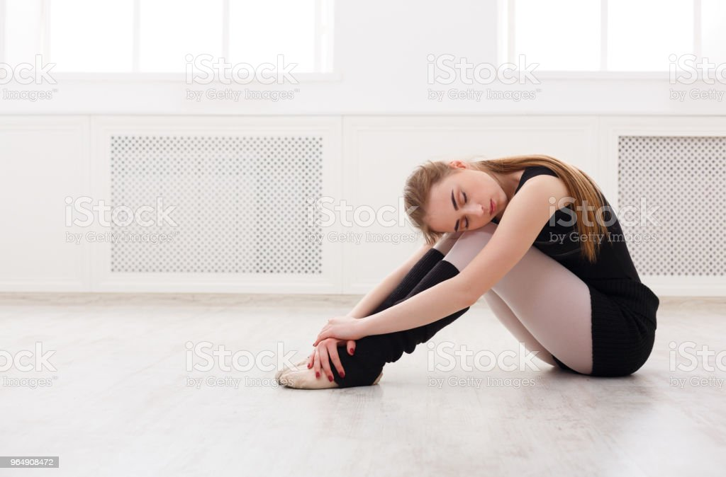 Classical ballet dancer sitting in white training class royalty-free stock photo