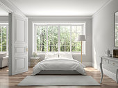 Classical bedroom and living room 3d render,The rooms have wooden floors and gray walls ,decorate with white and gold furniture,There are large window looking out to the nature view.