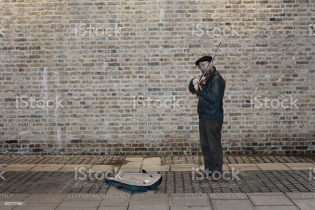 Classical busker against a brick wall stock photo