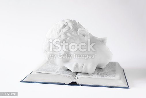A plaster cast of a classical Roman or Greek statue on an open book.