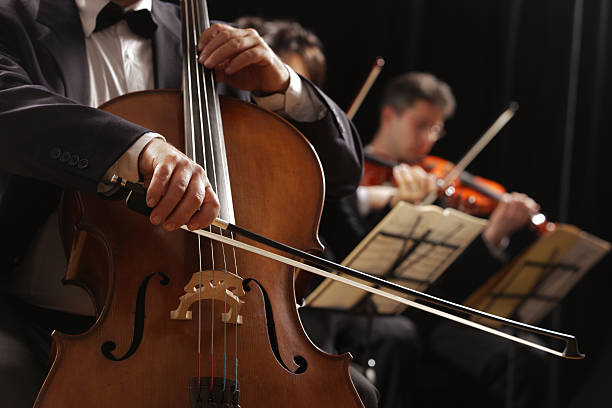 Classical music, cellist and violinists Symphony concert, a man playing the cello, hand close up string instrument stock pictures, royalty-free photos & images