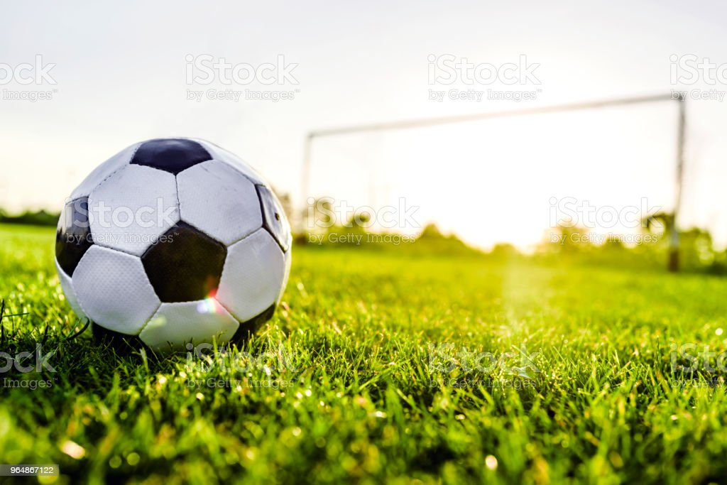Classical old football on the field and soccer goal royalty-free stock photo