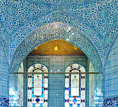 Classical oriental design  on wall with tiles and arched stained glass windows  at Topkapi Palace in Istanbul, Turkey.