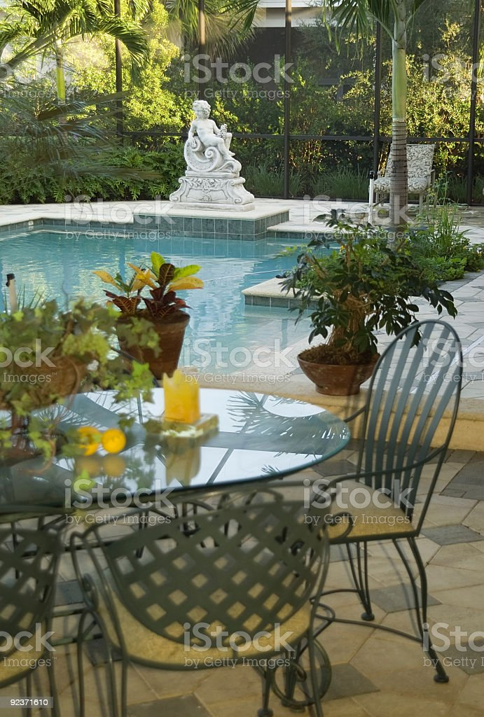 Classical Pool With Outdoor Dining Table and Chairs in Foreground royalty-free stock photo