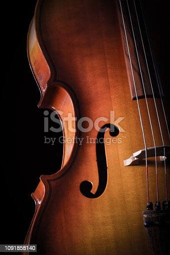 A high contrast color image of a classical style cello string instrument. The wood cello has vibrant color cut out on a black background.