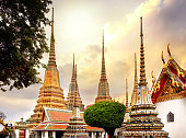 Classical Thai architecture in Wat Pho public temple at dramatic orange sunset sky , Bangkok, Thailand. Wat Pho known also as the Temple of the Reclining Buddha.
