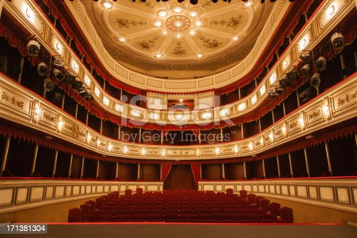 Classical Theater with Red stage curtain with arch lights and shadows.View from the stage