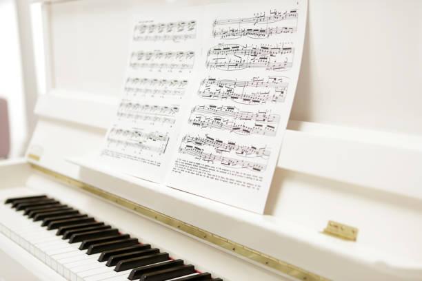 klassische weiße melodie - piano noten stock-fotos und bilder