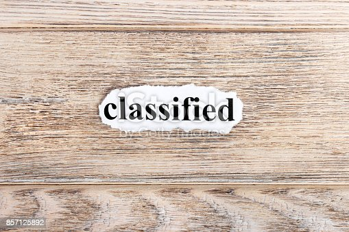 1070355804 istock photo classified text on paper. Word classified on torn paper. Concept Image 857125892