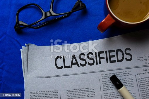 1070355804 istock photo Classifieds text in headline isolated on blue background. Newspaper concept 1186776997